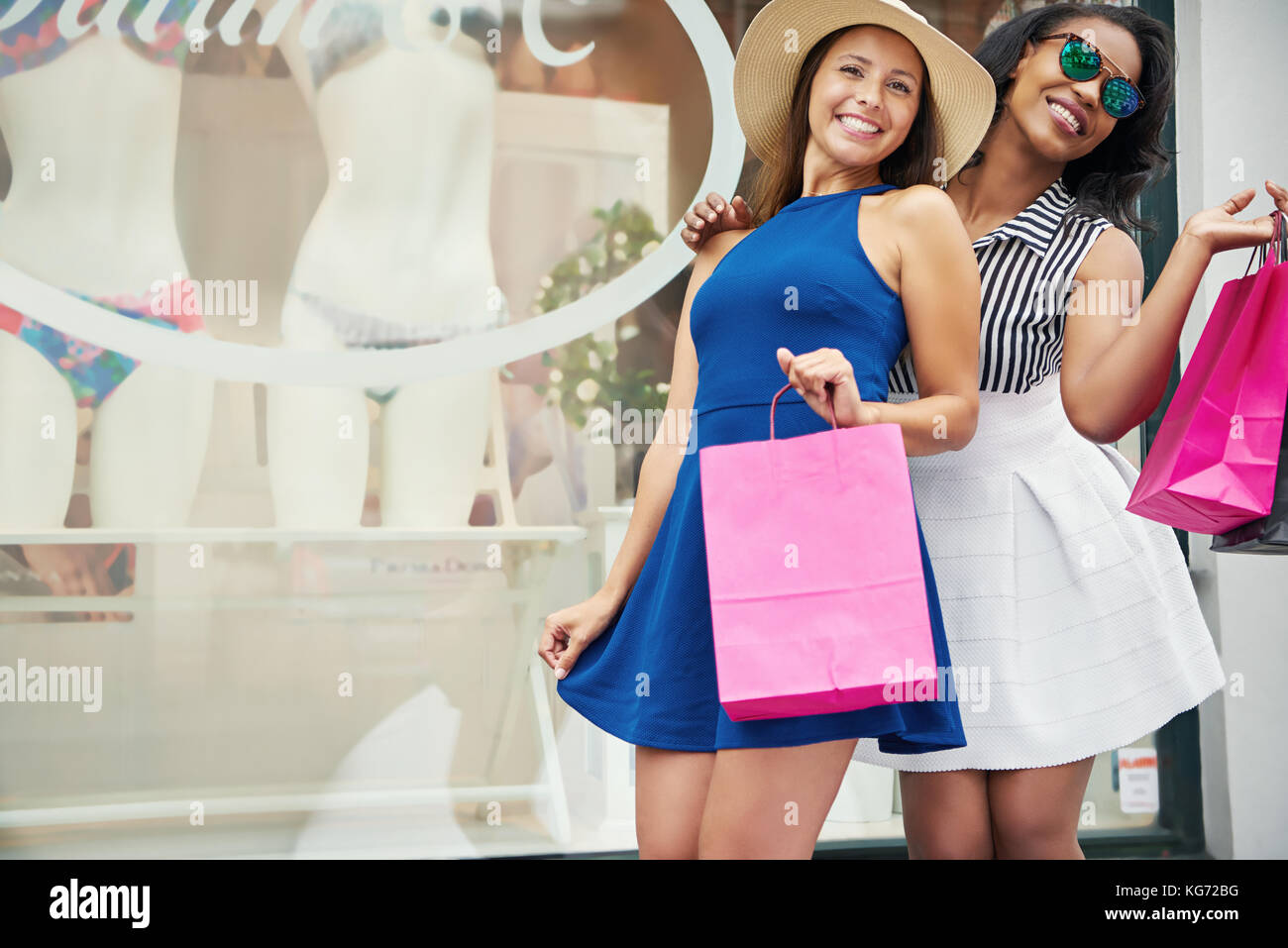 Pair of beautiful young adult women in short skirts holding pink shopping bags with copy space - Stock Image