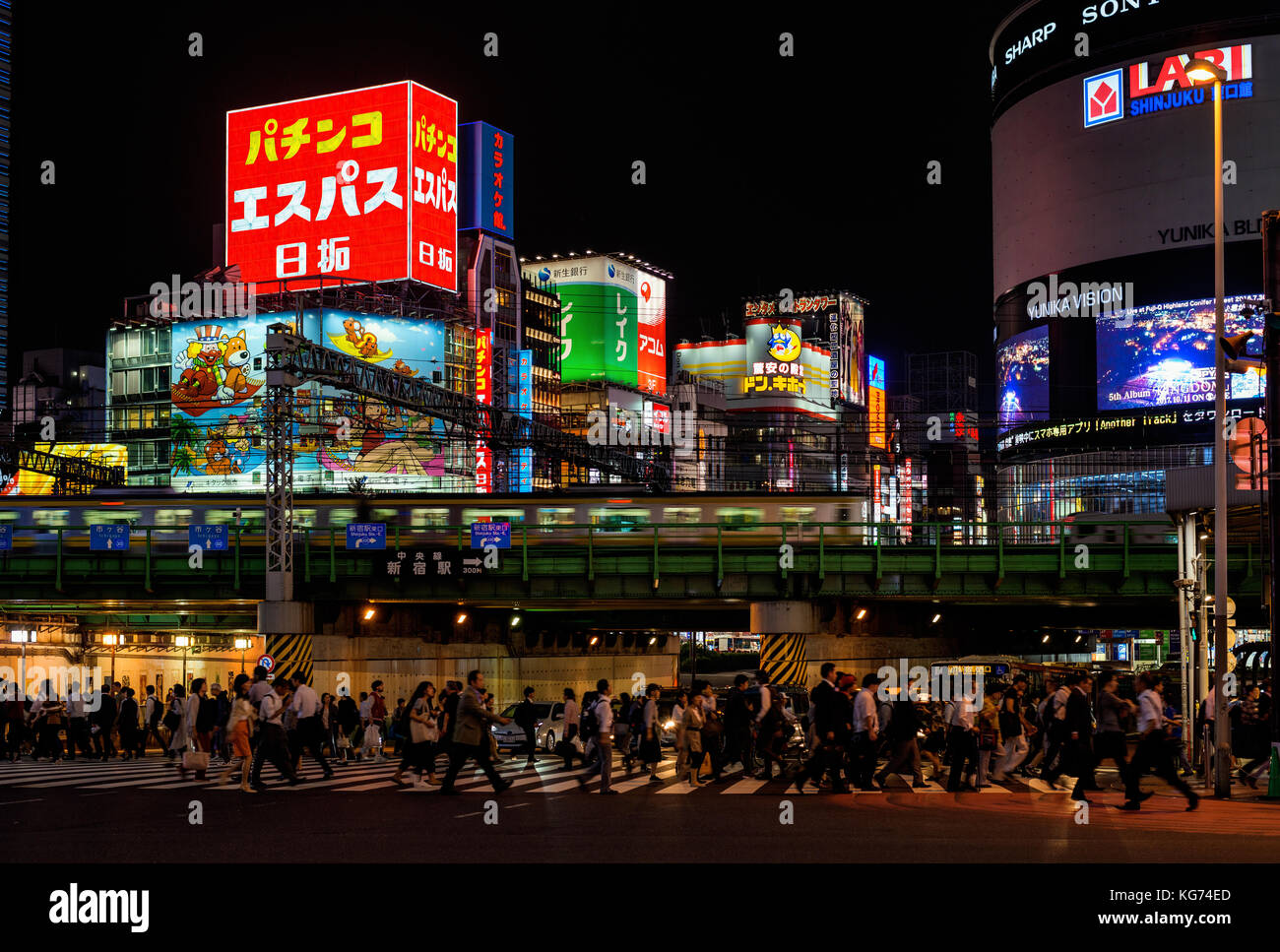 Night life in Tokyo. People cross a very busy crossroad below Shinjuku district lights - Stock Image