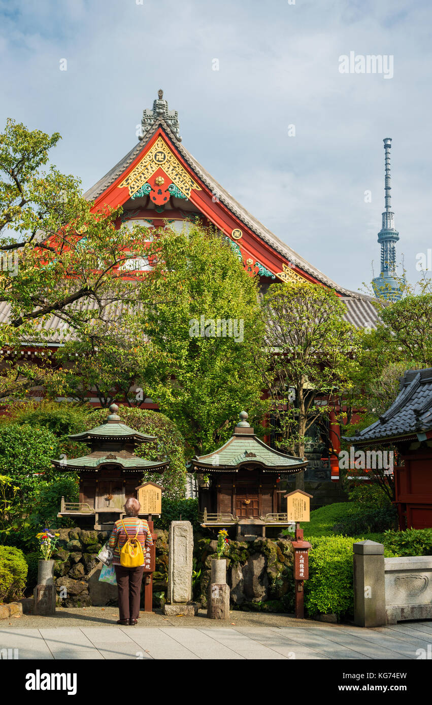 Tradition and Modernity in Japan. People pray in an old temple below modern Skytree Tower in Tokyo. - Stock Image
