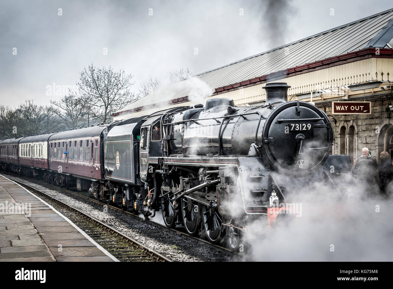 A steam locomotive pulls into the platform at Ramsbottom Station on The East Lancs Railway - Stock Image
