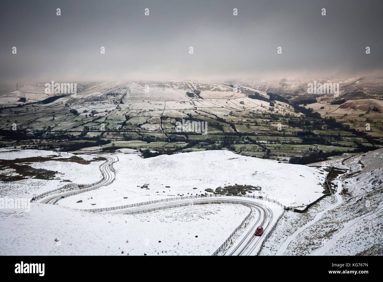A car drives up a snow covered mountain road in winter. Edale valley, Peak District, UK Stock Photo