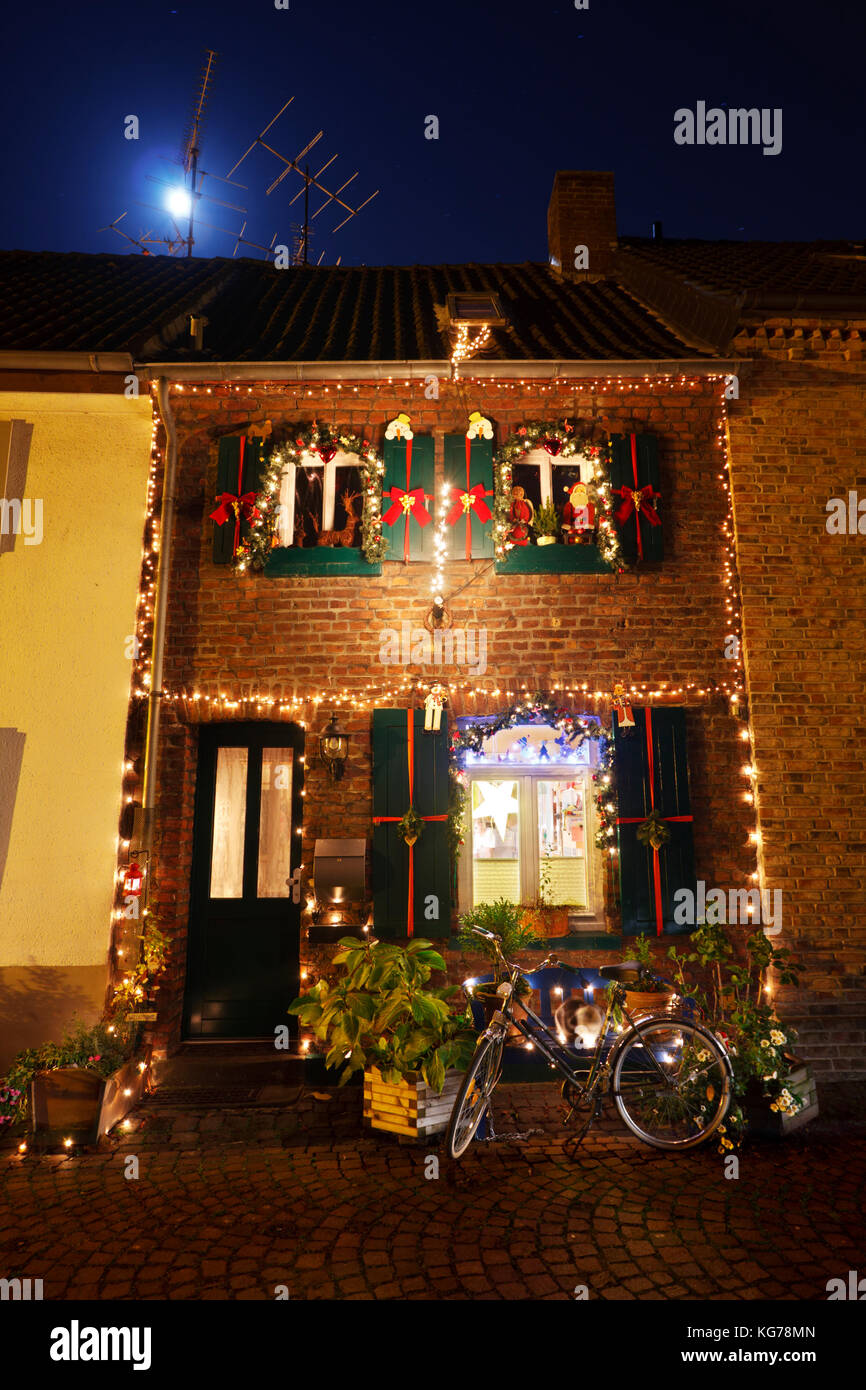 A small town house with christmas decoration at night, the moon shining above. - Stock Image