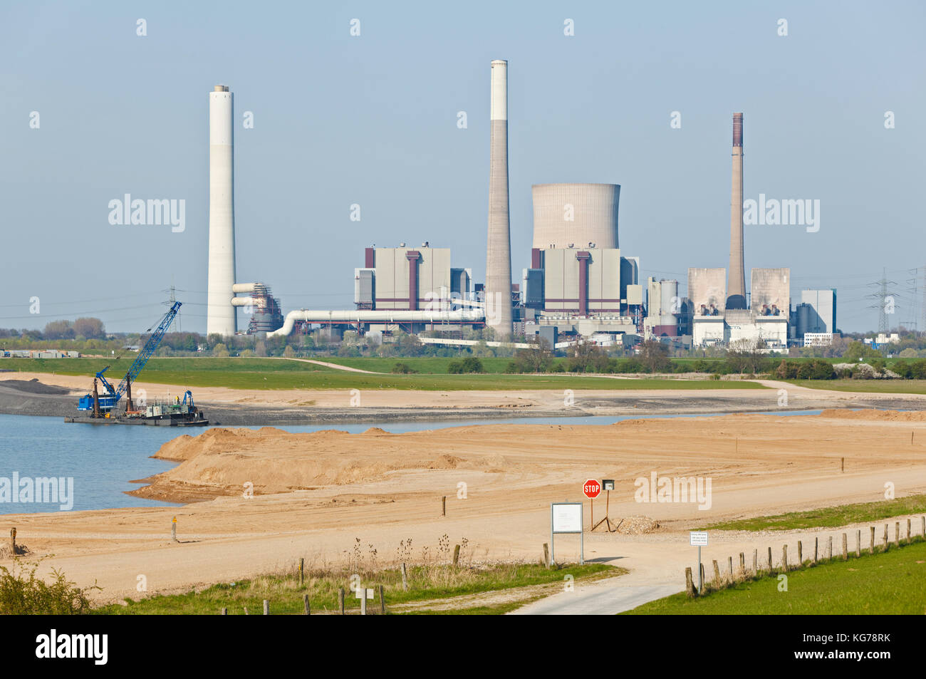 Gravel industry landscape in front of a large power station at the Rhine River. - Stock Image