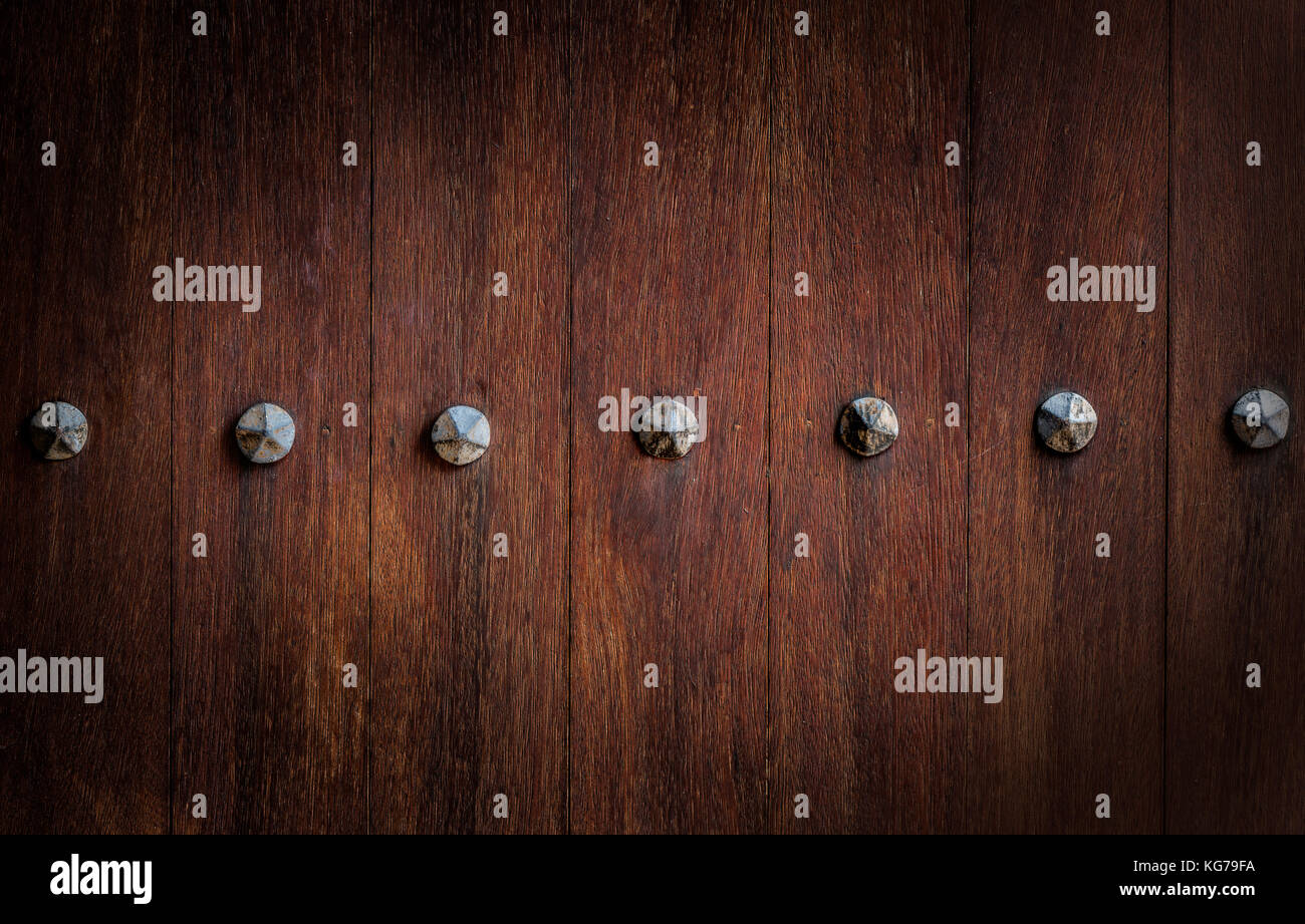 Section of ancient wooden door with  rusty metal nail heads - Stock Image