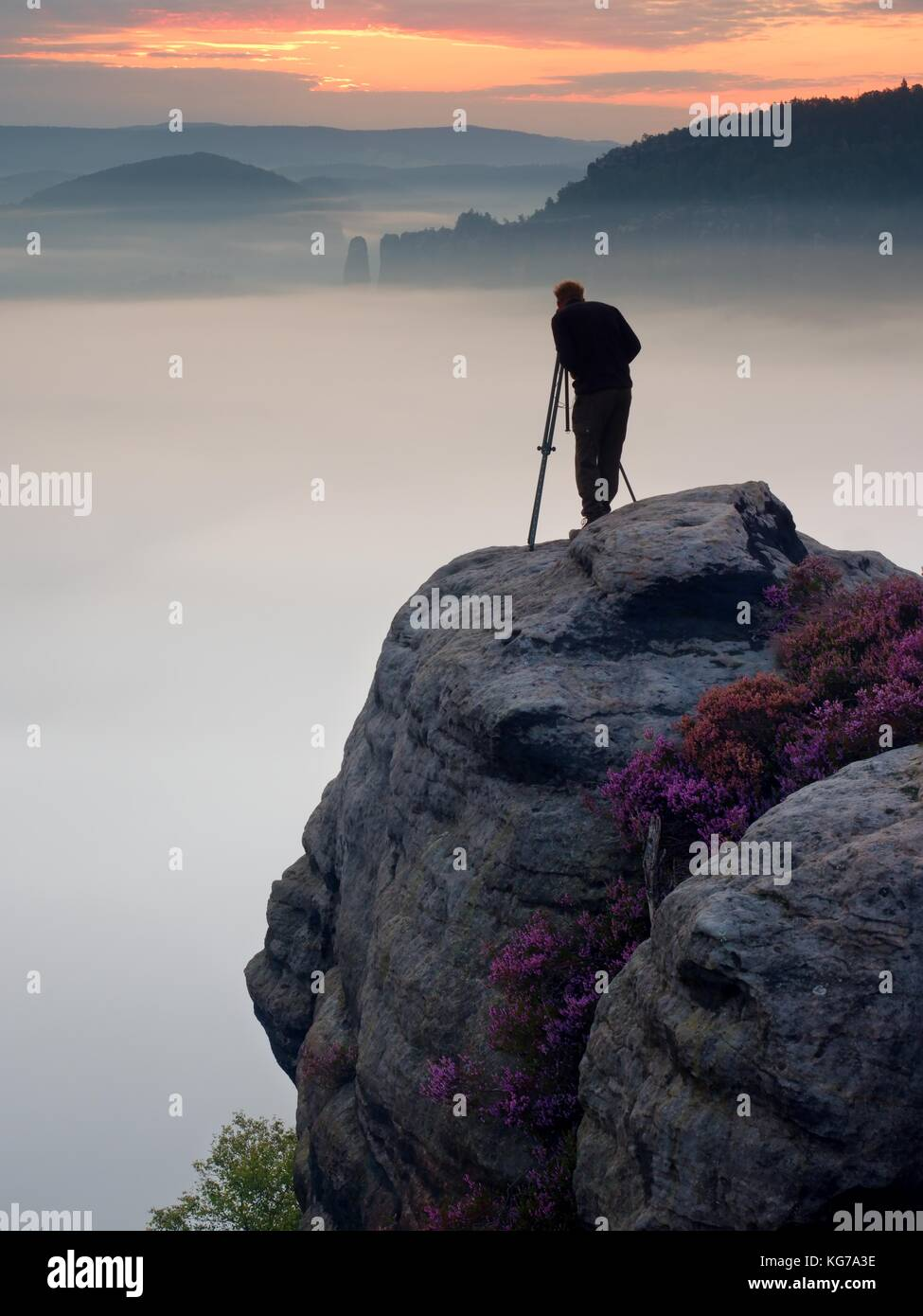 Professional photographer takes photos with mirror camera and tripod on peak of rock. Dreamy fogy landscape, spring - Stock Image