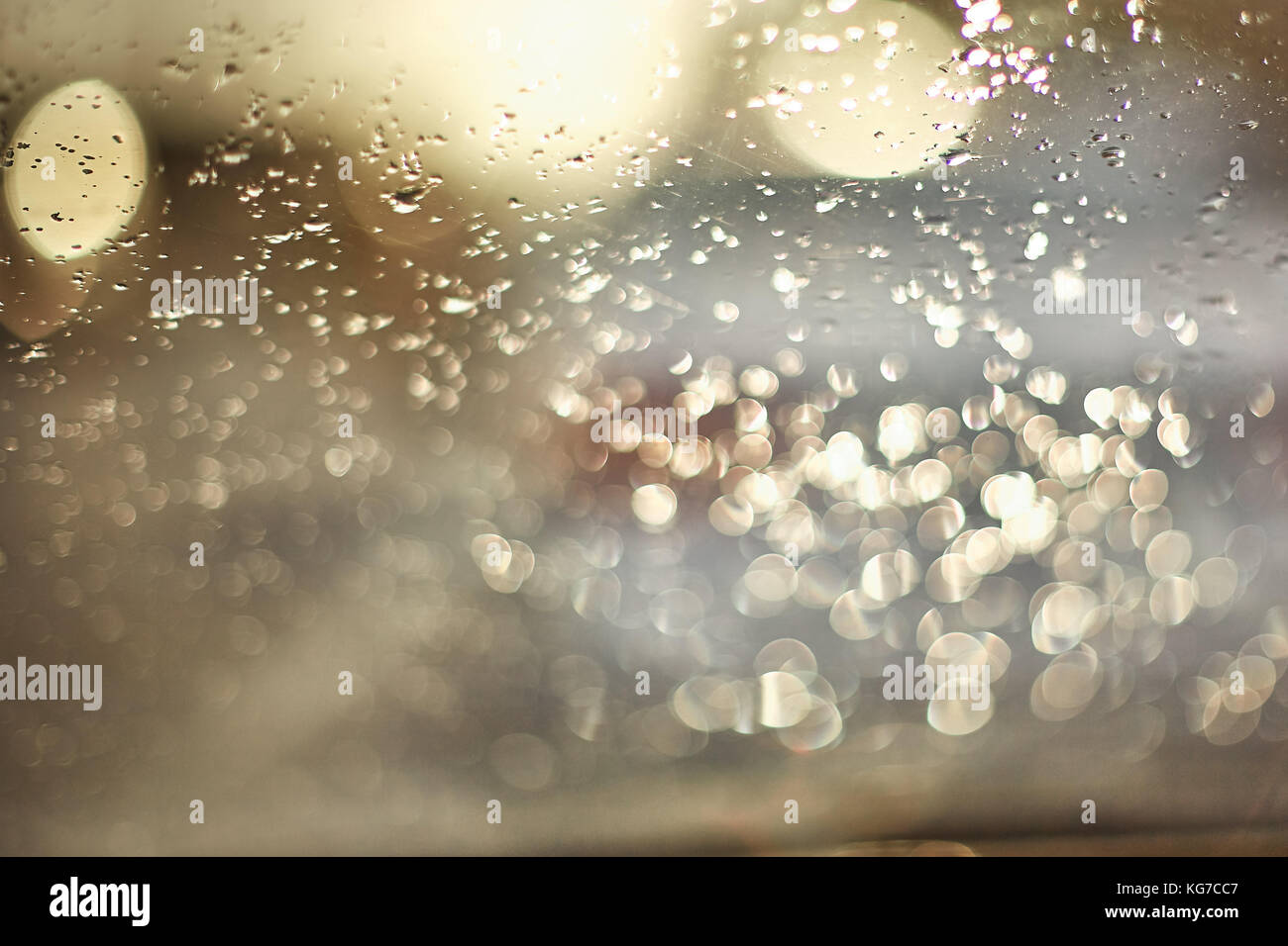 Drops of water on the surface of the glass during sunset. In the photo there are glare from objects, the photo is - Stock Image
