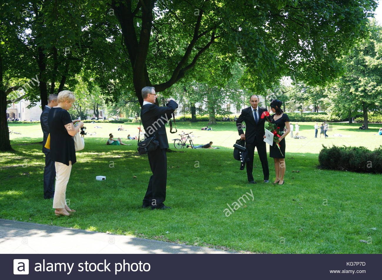 POZNAN, POLAND - JUNE 09, 2013: Parents making images of their graduated daughter at a park in the center of Poznan, - Stock Image
