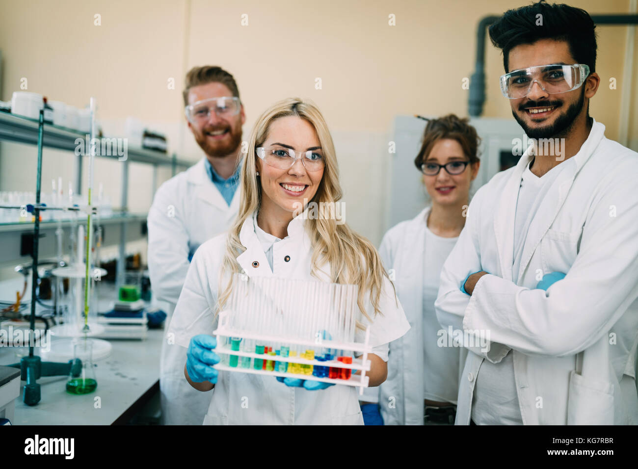Group of young successful scientists posing for camera - Stock Image
