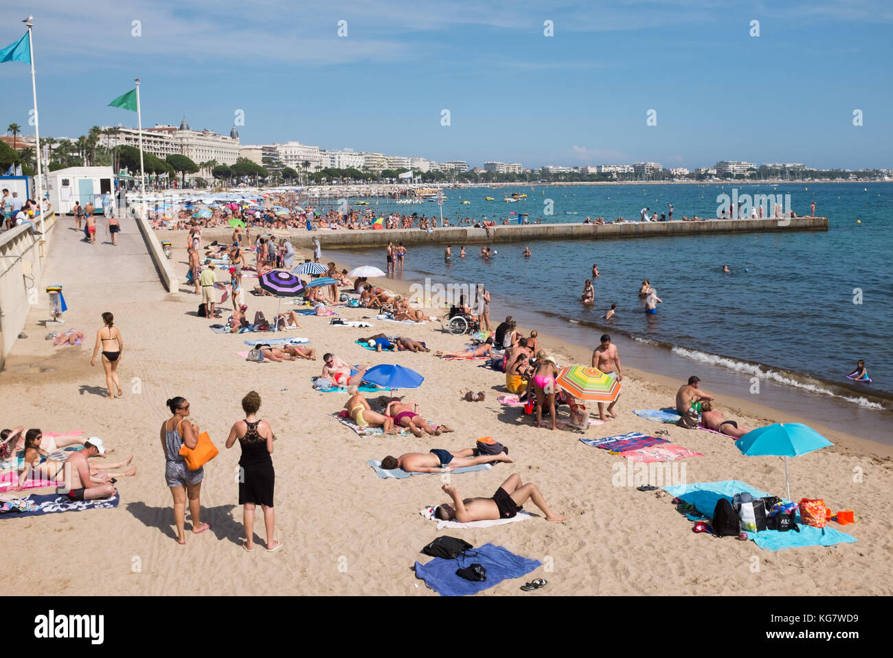 People enjoying sunbathing and swimming at beach along Boulevard de la Croisette, Cannes, Cote d'Azur, Provence-Alpes-Cote d'Azur, France. Stock Photo