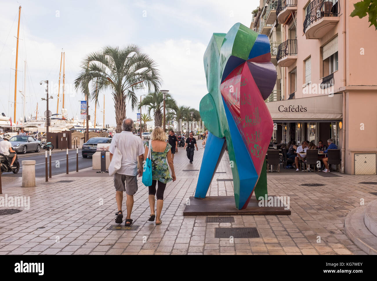 Tourists walking on pavement near colourful sculpture at Quai Saint Pierre, Cannes, Cote d'Azur, Provence-Alpes - Stock Image