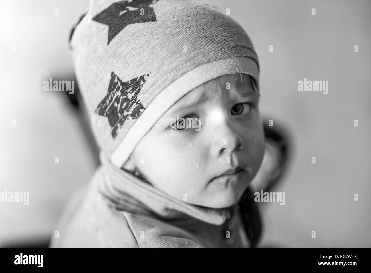 Portrait of a little girl who cries, runny nose, at home - Stock Image