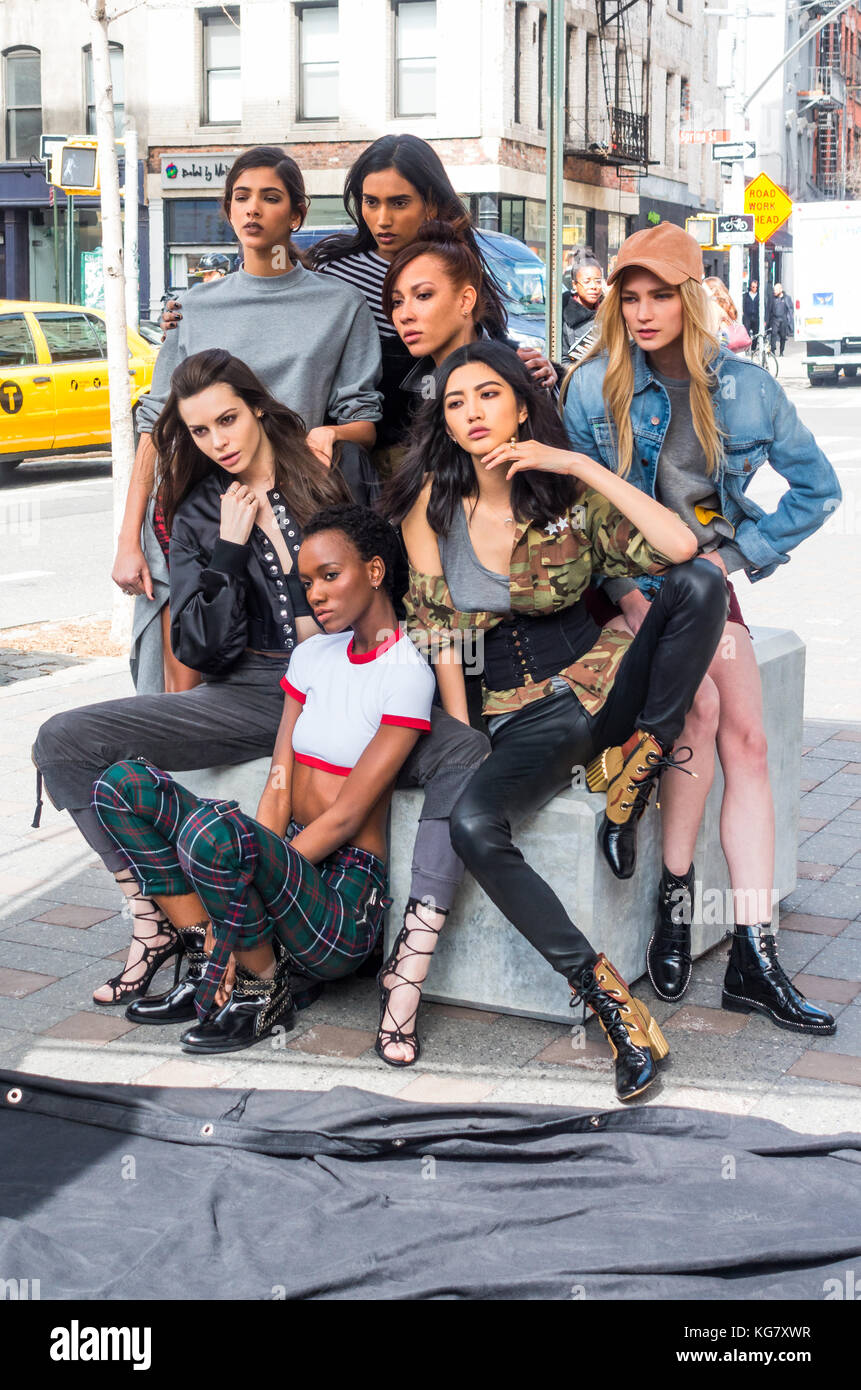 Seven female models posing for a photographer on a New York City street - Stock Image