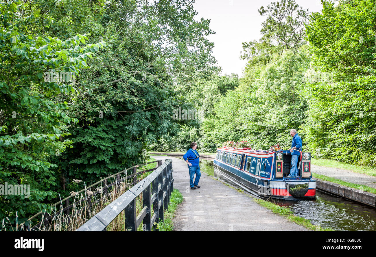 A man and woman navigate a barge along the Llangollen Canal - Stock Image