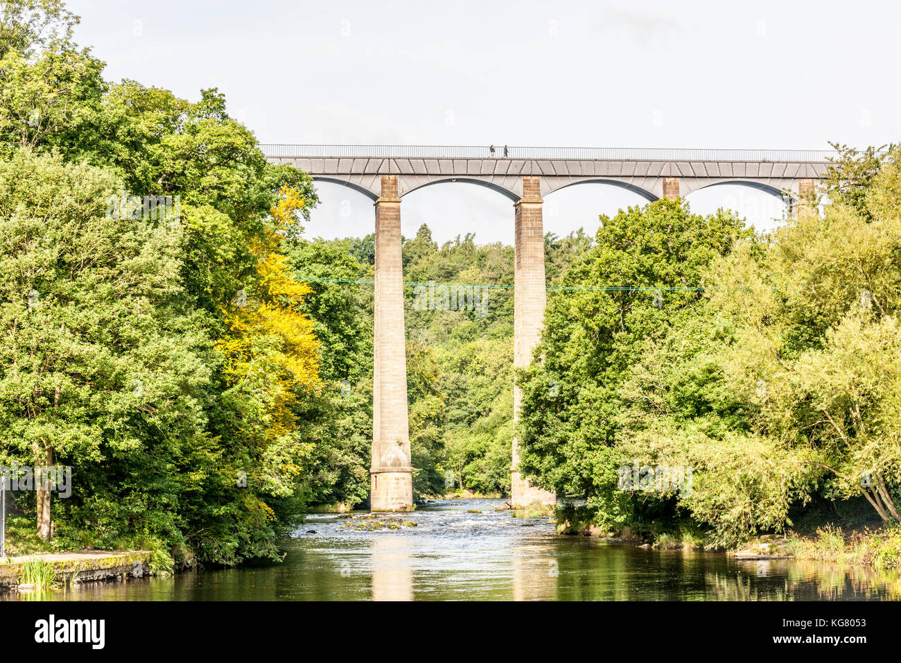 Two people walk along the Pontcysyllte Aqueduct as it carries the Llangollen Canal over the River Dee in Llangollen, Stock Photo