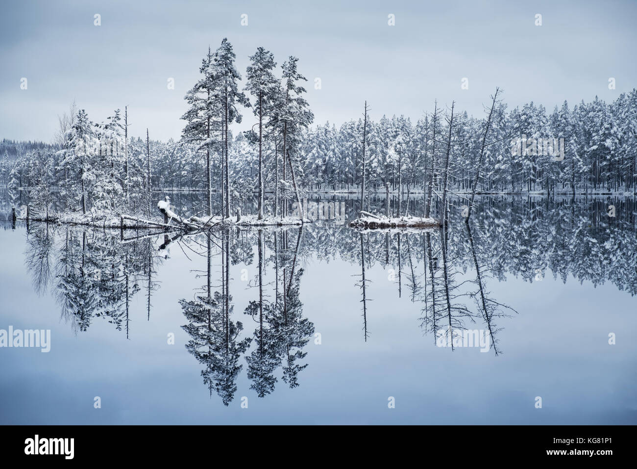 Scenic landscape with lake reflection and snow at winter evening - Stock Image