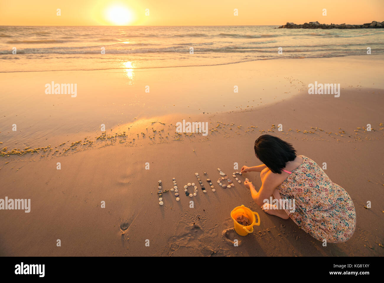 Woman writing Holiday text on sand at the beach - Stock Image