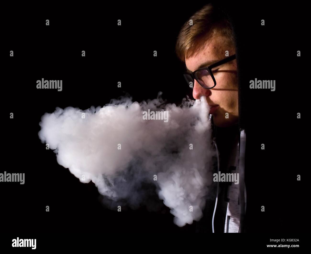 Young man smoking electronic cigarette on black background - Stock Image