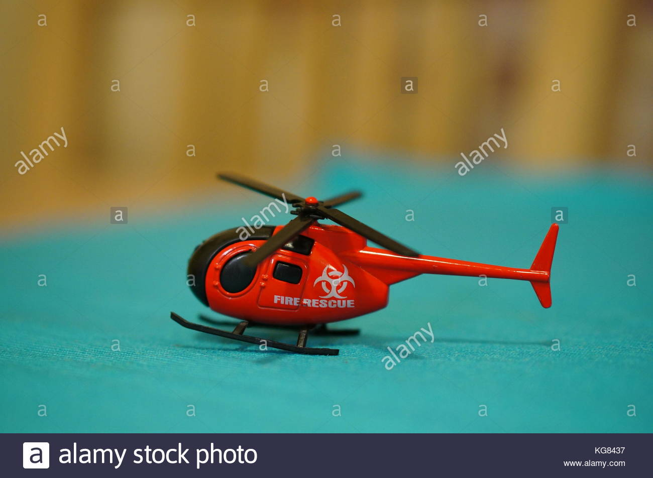 Red Fire Rescue toy helicopter on a blue surface in soft focus - Stock Image