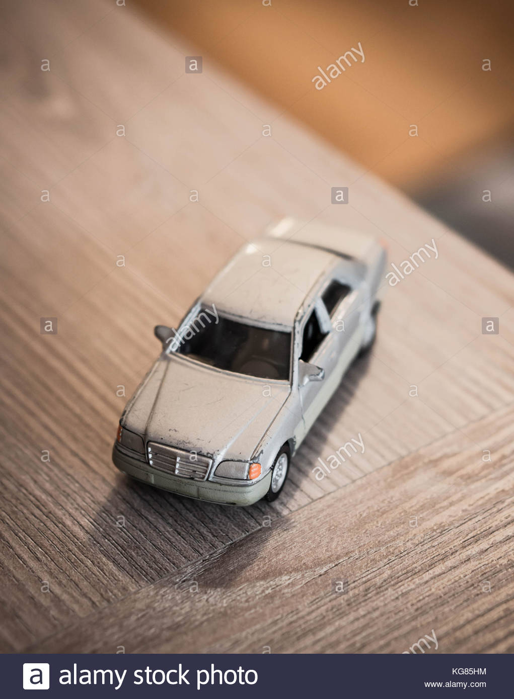 Old metal silver toy model Mercedes Benz car on a wooden table in soft focus - Stock Image
