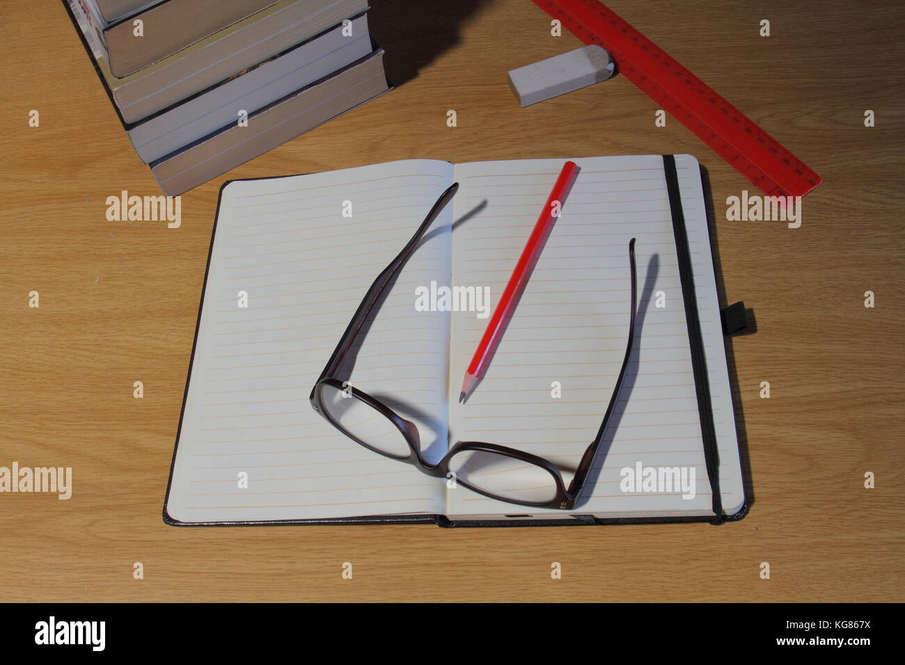 View from above of a desk with study materials and aids in landscape format - Stock Image