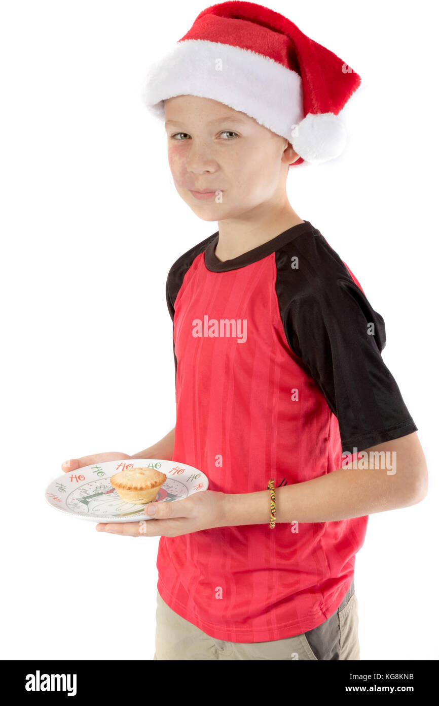 Pre-teen boy in christmas hat and a mince pie - Stock Image