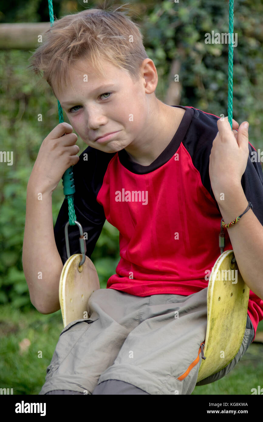 Sad pre-teen boy sitting on a swing outside - Stock Image