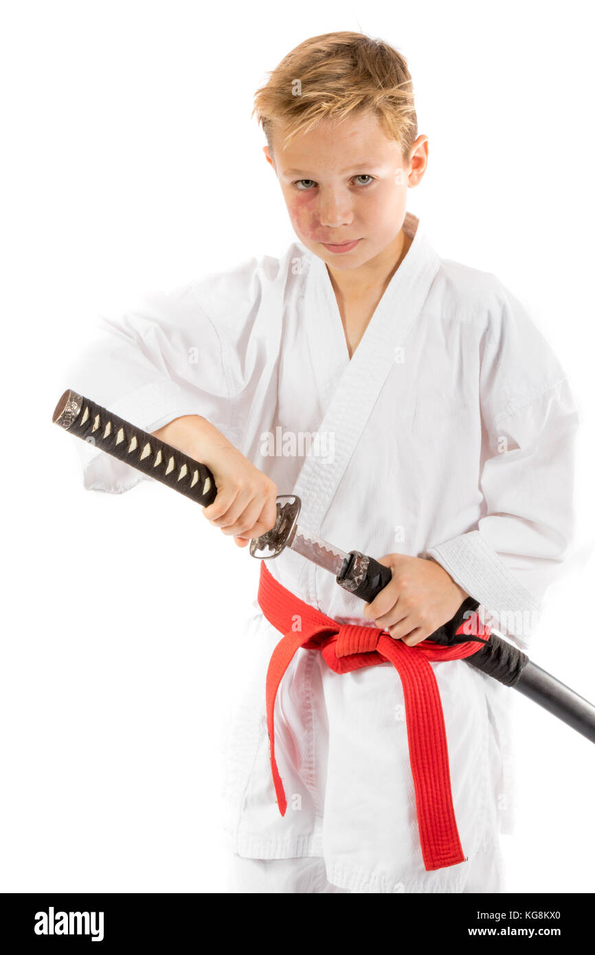 Pre-teen boy with a samurai sword isolated on a white background - Stock Image