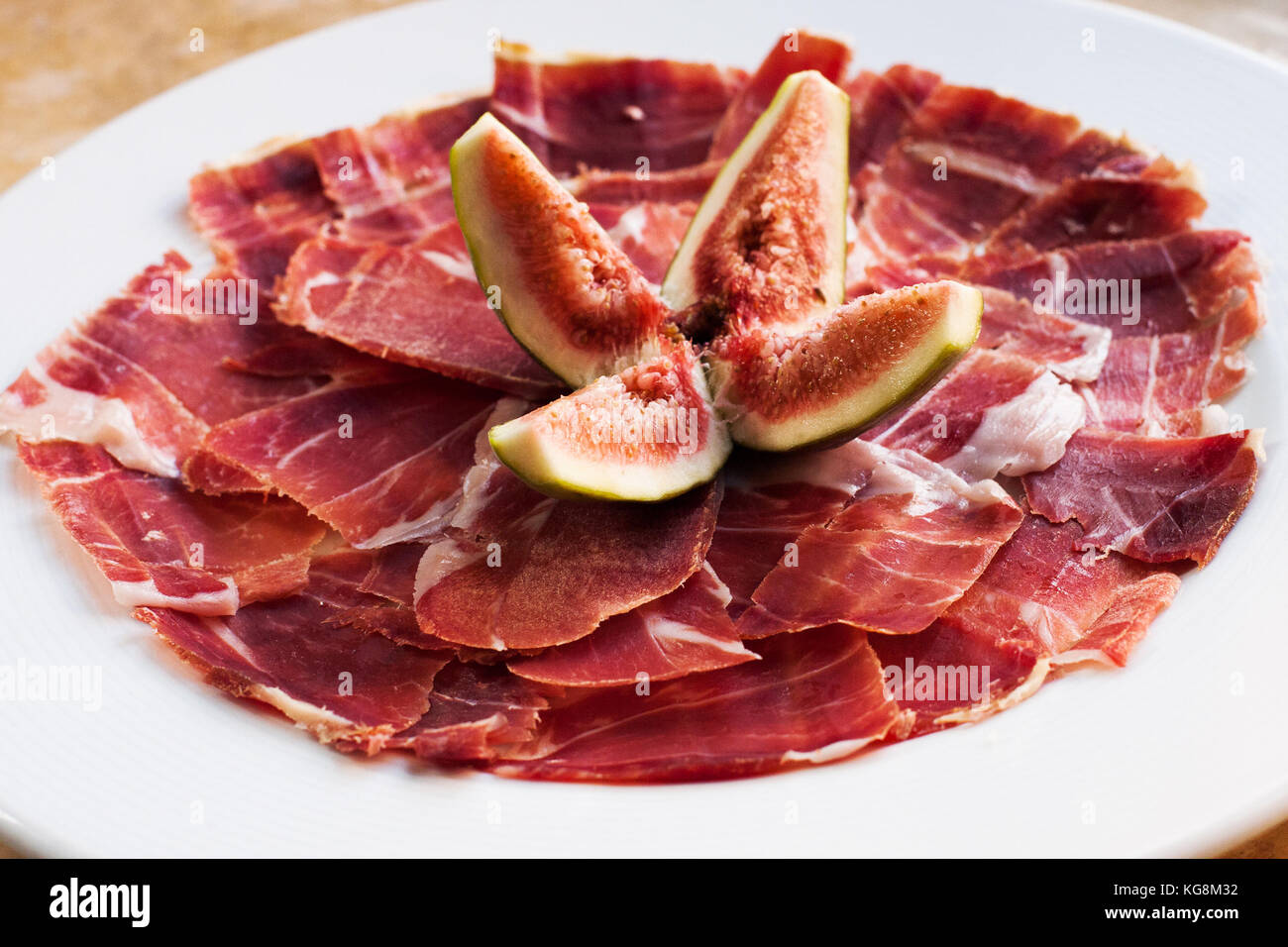 Spanish Cuisine tapas food Jamon with fig. Beautiful appetite slices of raw pork meat, white plate background. Stock Photo