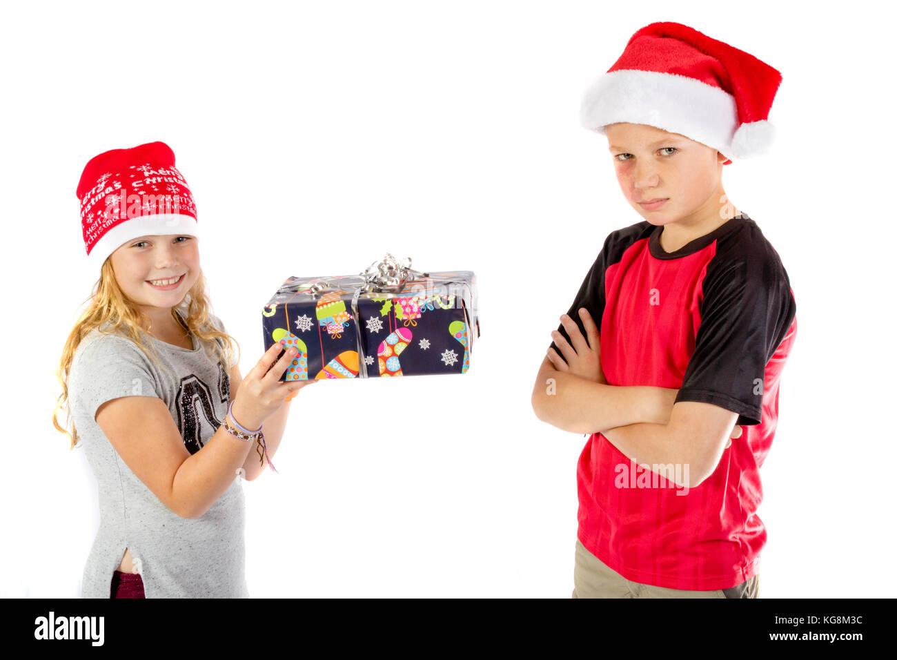 Grumpy boy given a christmas present - Stock Image
