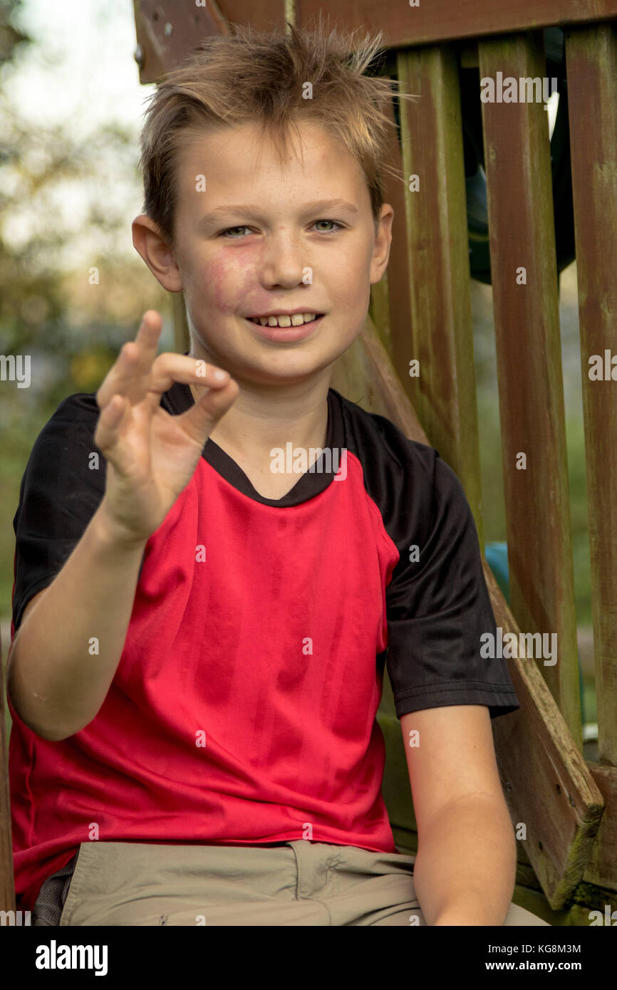 Pre-teen boy giving ok gesture sitting outside - Stock Image