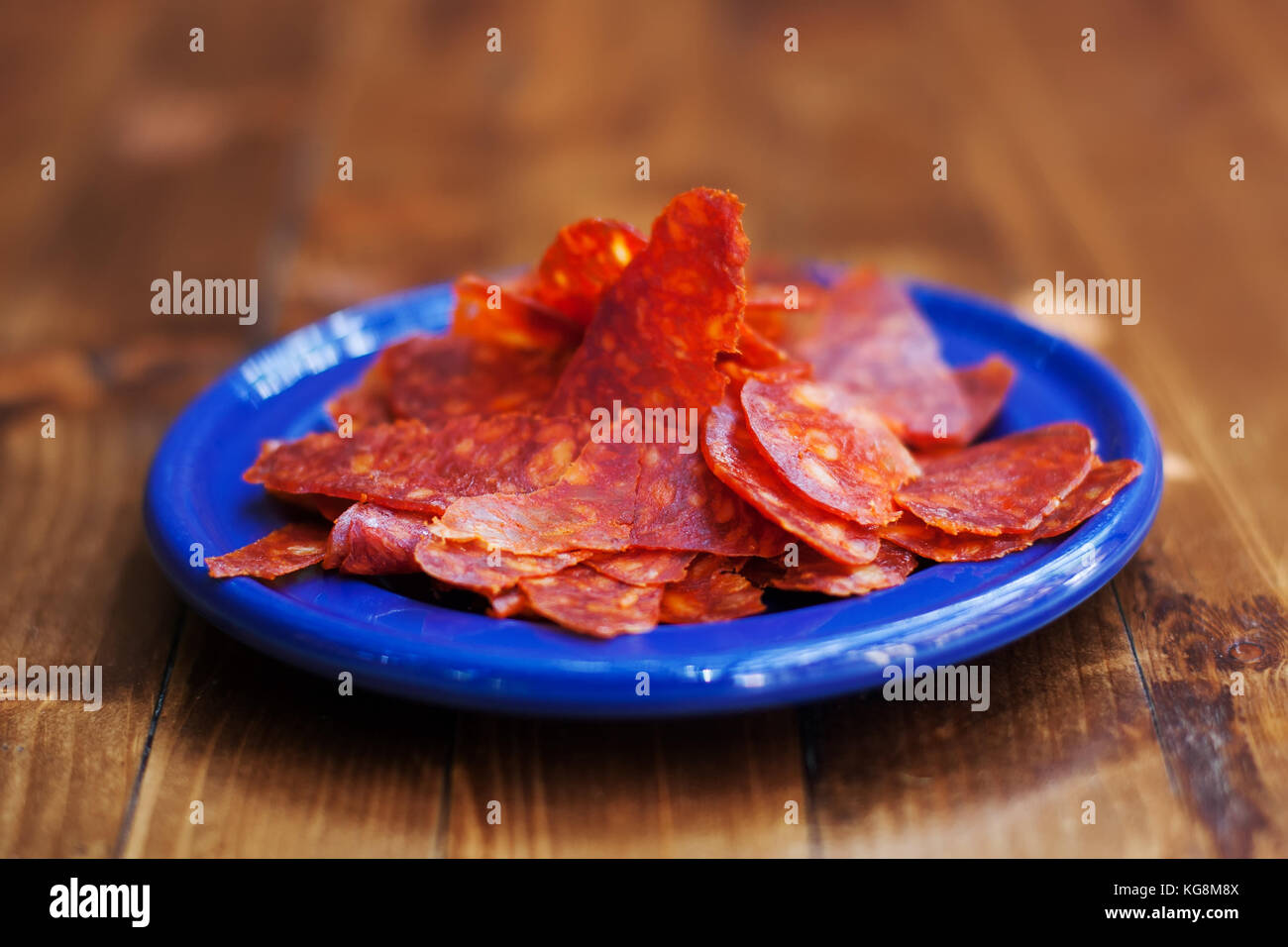 Spanish cuisine tapas Chorizo sausage slices in blue plate. Textured smoked spicy pork meat. Close-up photo, soft - Stock Image