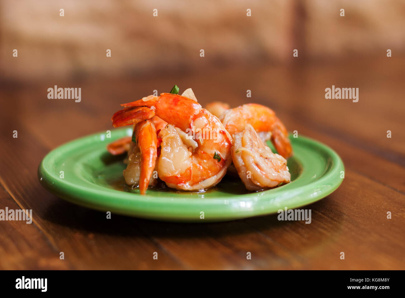 Pickled marinated shrimp in a green plate. Traditional mediterranean cuisine food, spanish tapas. Wooden table, - Stock Image
