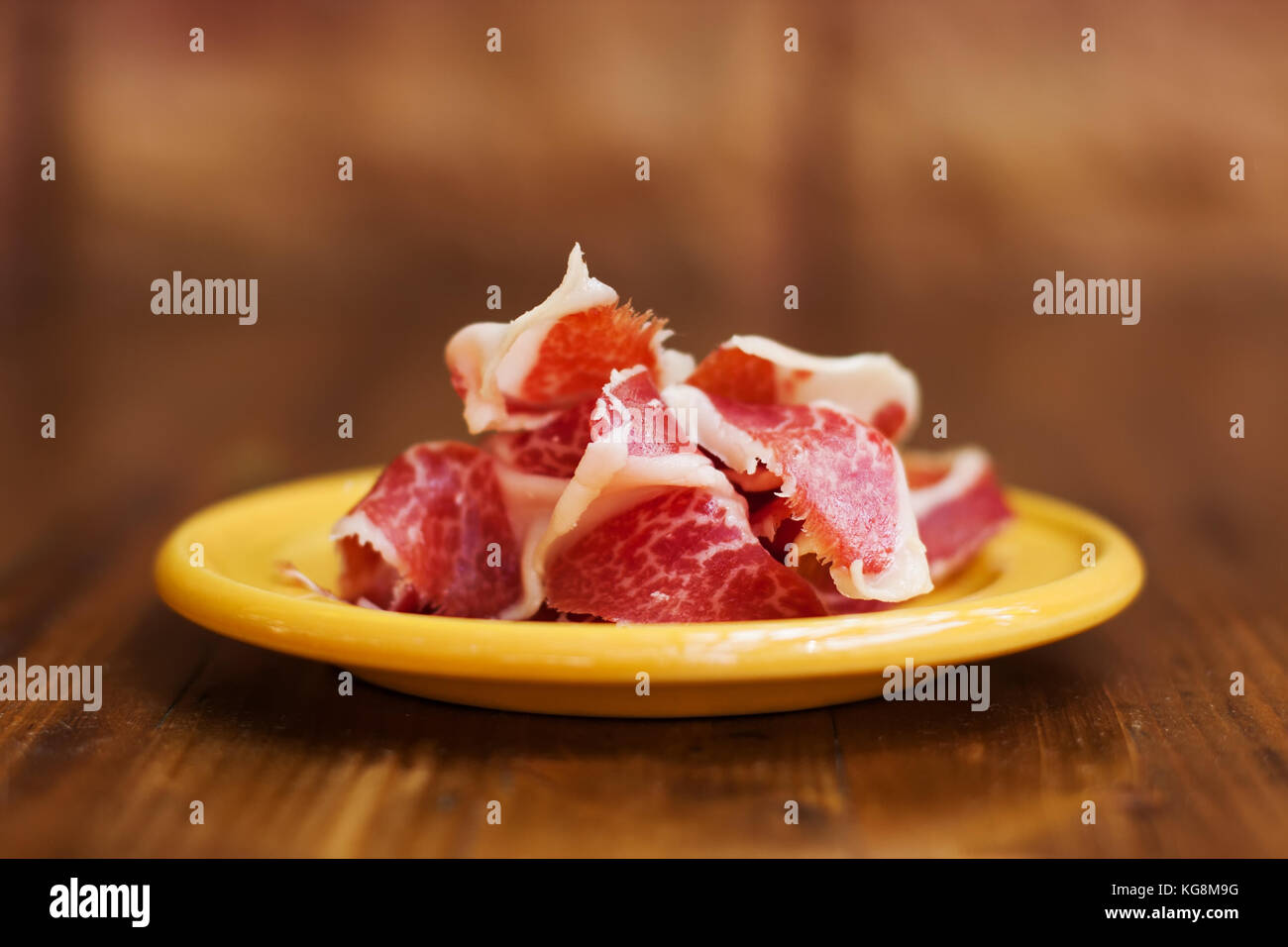 Spanish cuisine tapas food Jamon in a yellow plate. Beautiful appetite slices of raw pork meat. Close-up photo, - Stock Image