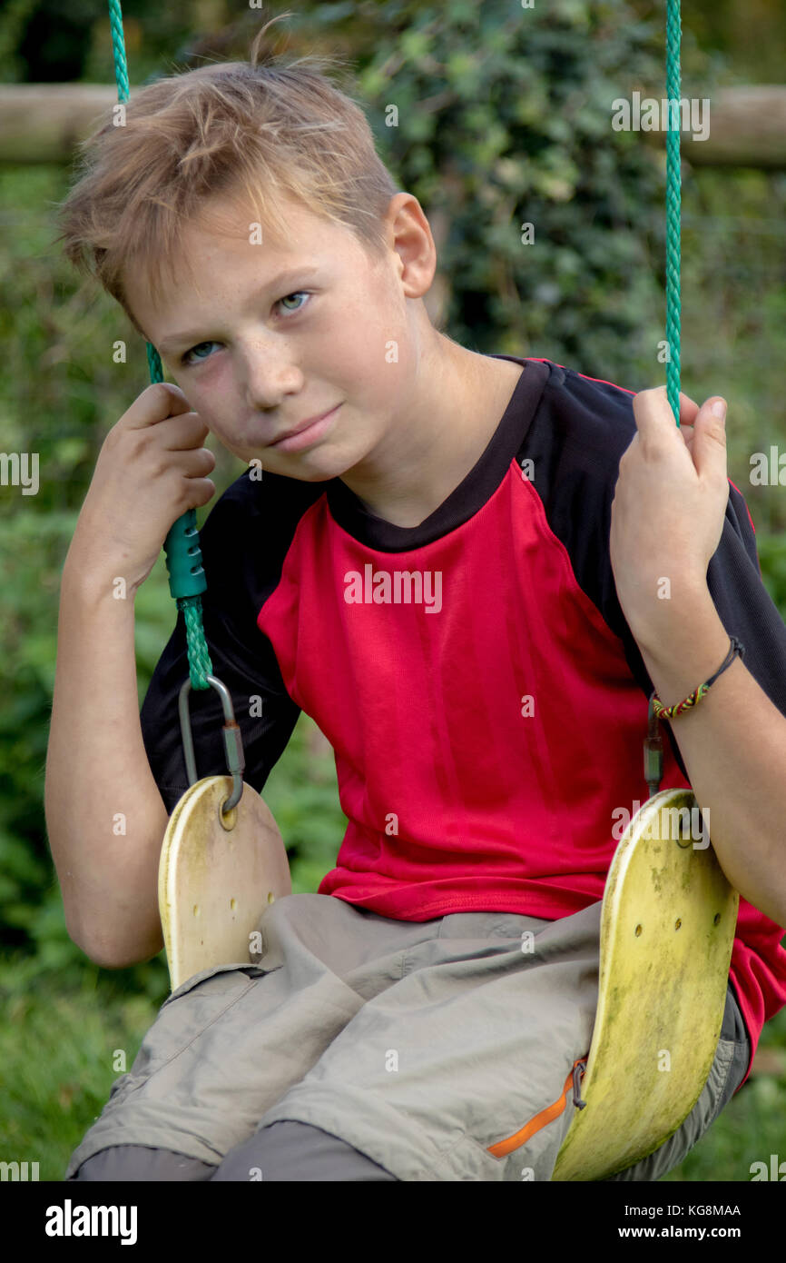 Sad pre-teen boy sitting on a swing outside Stock Photo
