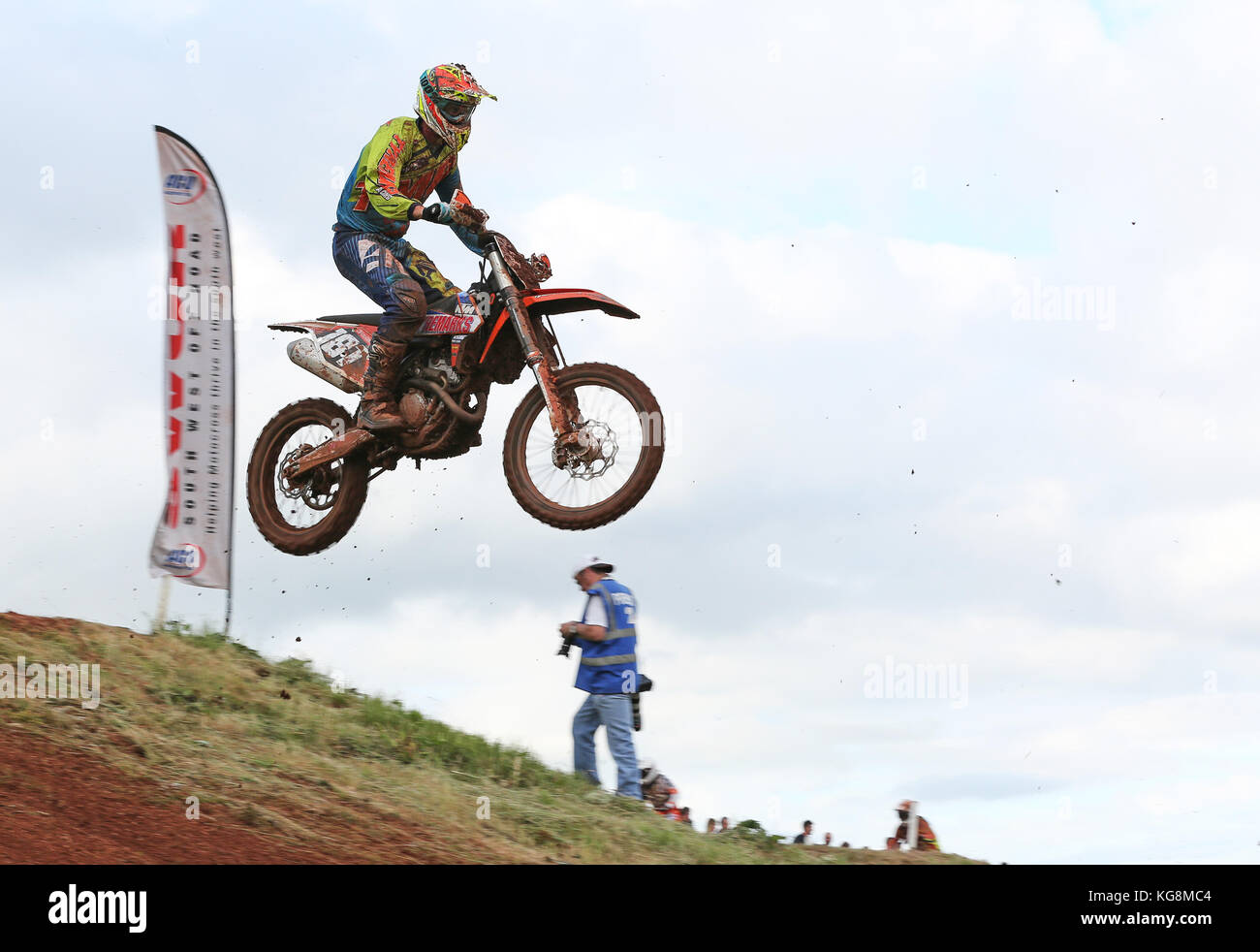 Motocross bike Jumping with photographer in the background - Stock Image