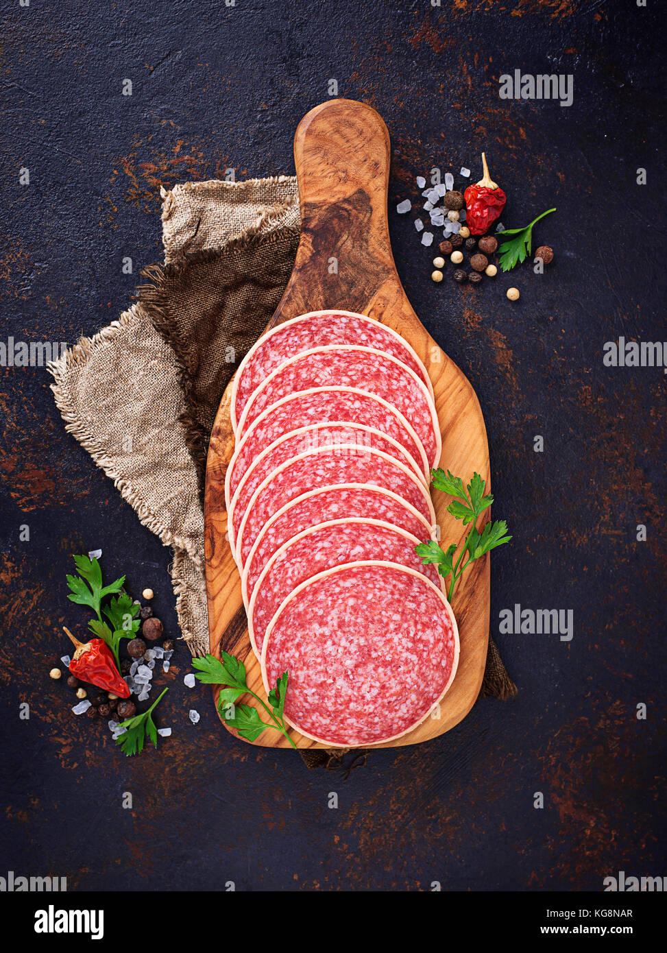 Italian salami sausage on wooden board. - Stock Image