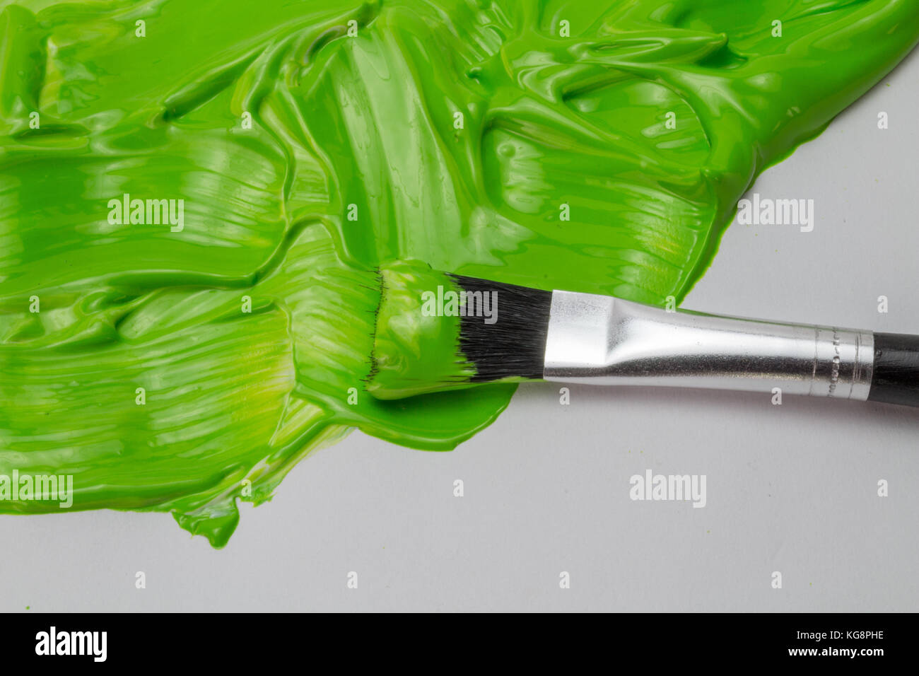 Green Paint And Art Brush With Thick Glossy Strokes On White