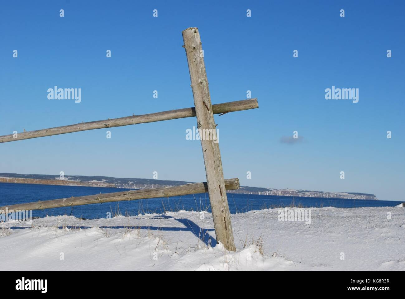 Fence post and two rails of an old, disused fence along the shoreline, Conception Bay South, Newfoundland - Stock Image