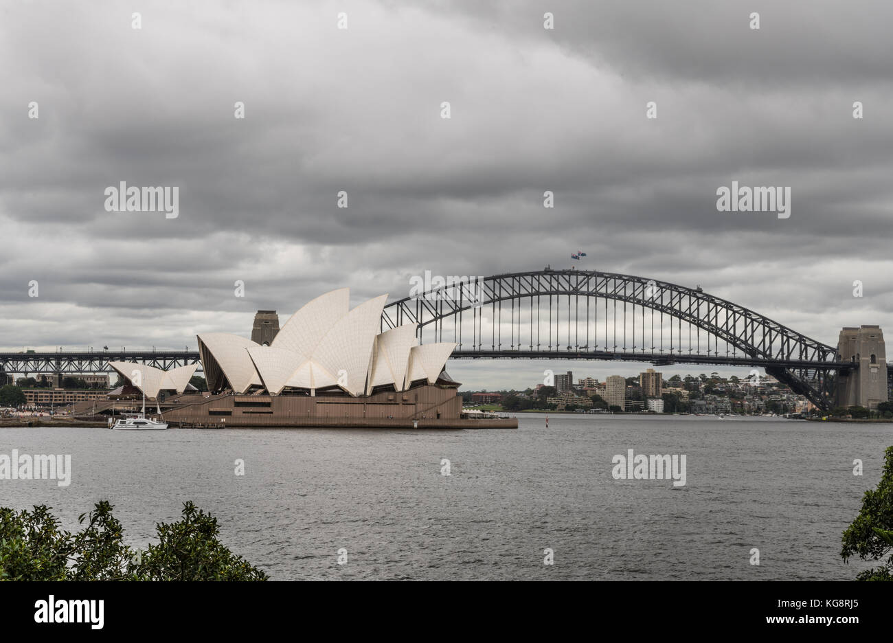 Sydney, Australia - March 23, 2017: White Opera House and black bow of Harbour Bridge behind under heavy rainy cloudscape. - Stock Image