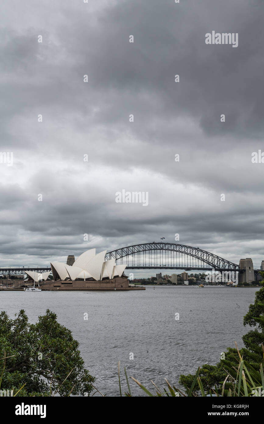 Sydney, Australia - March 23, 2017: Portrait of white Opera House and black bow of Harbour Bridge behind under heavy - Stock Image