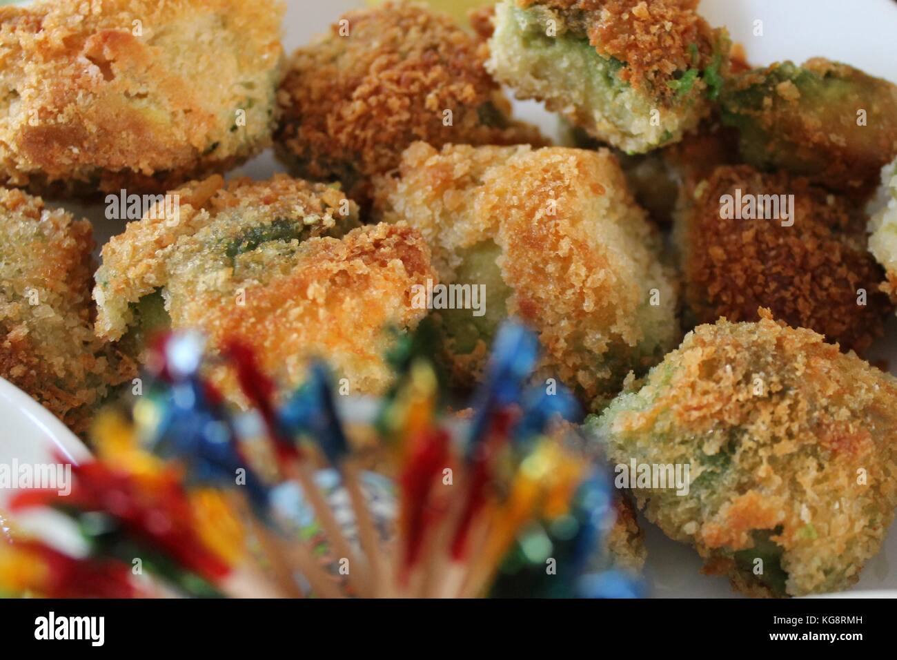 Breaded deep fried dill pickles on a white serving dish, with decorative, colorful toothpicks. - Stock Image