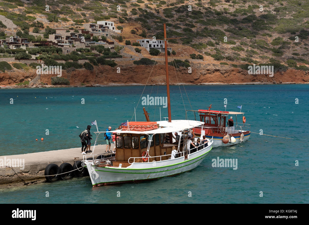 The seaside resort of Plaka with passengers boarding a small ferry to Spinalonga Island, former Leper Colony. Northern - Stock Image