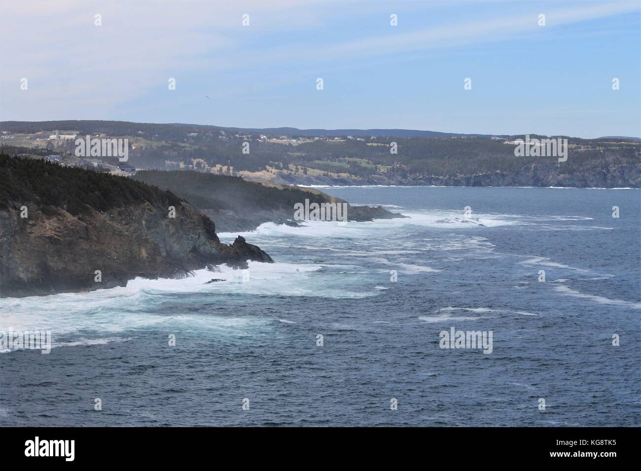 Waves breaking against the cliffs, Logy Bay-Middle Cove-Outer Cove, Newfoundland and Labrador, Canada. Light fog, - Stock Image