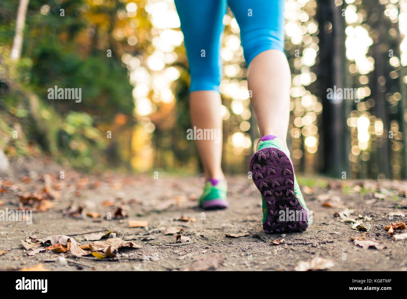 Woman walking and hiking in autumn forest, sport shoes. Jogging, trekking or training outside in autumn nature. - Stock Image