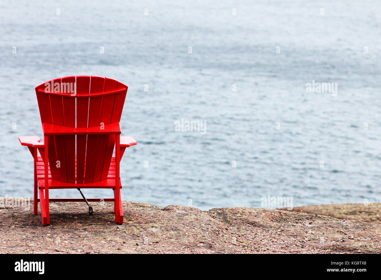 A red Adirondack chair anchored to the cliff, facing out toward the sea, trail side, Signal Hill, St. John's, Newfoundland Stock Photo