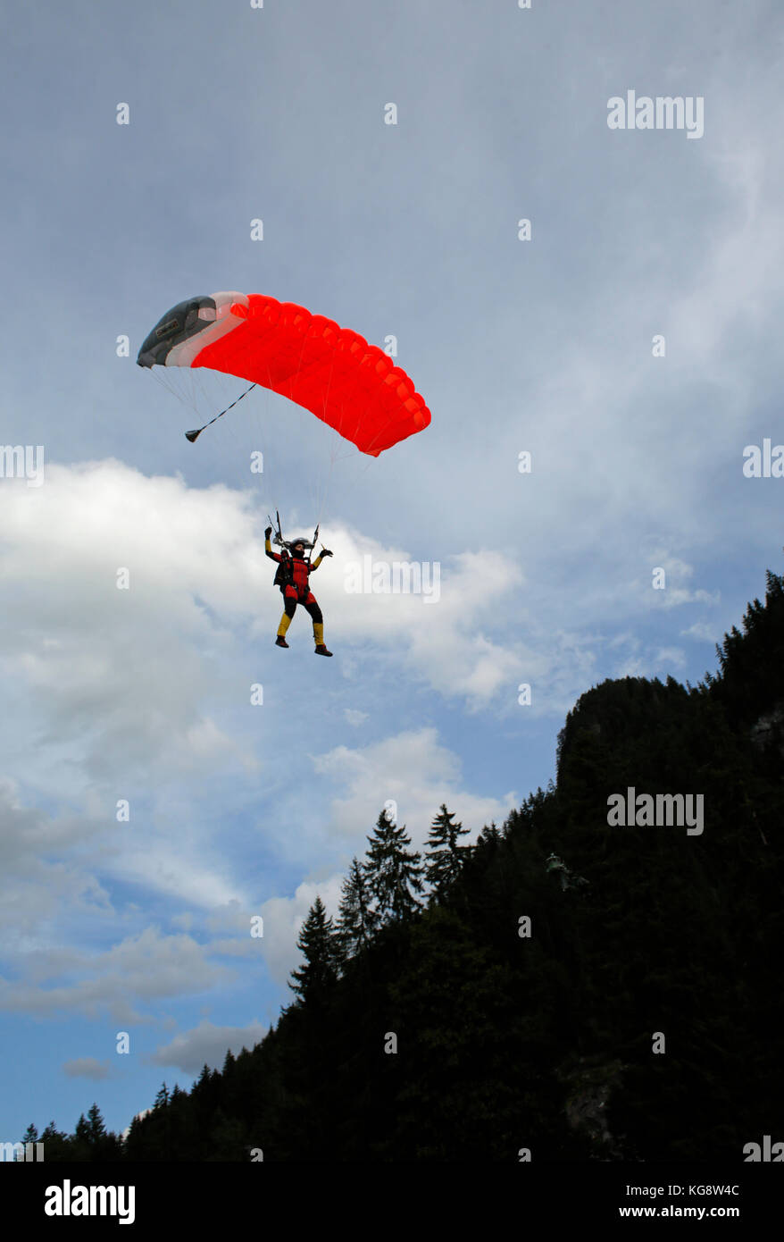 Skydiver under canopy is flying in the sky and approaching the landing area. Soon the jumper is stepping down and - Stock Image