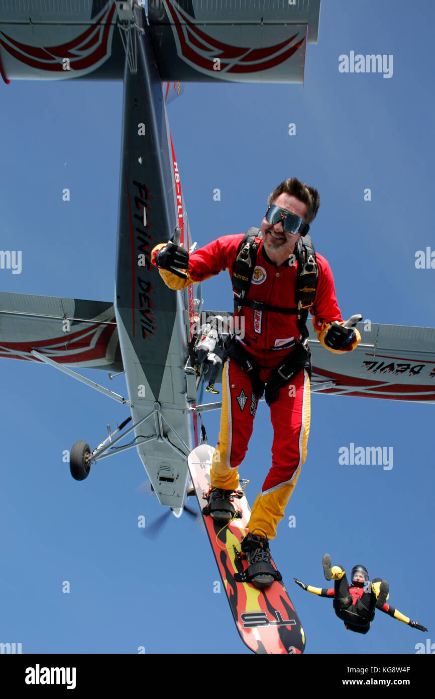 Skysurfer is exiting from an aircraft with a big smile on his face. He is flying high in the sky and having fun - Stock Image