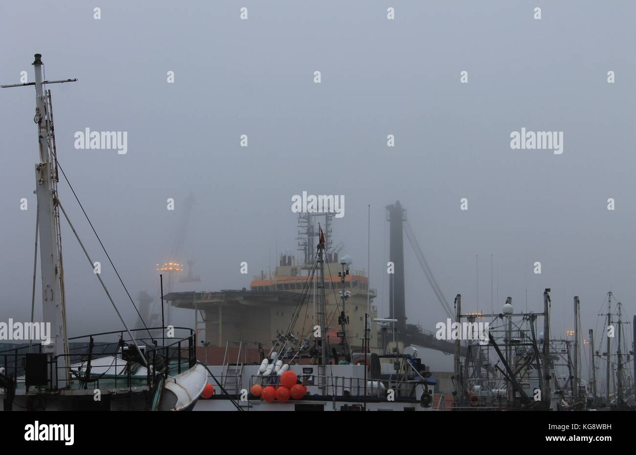 Boats in the fog, St. John's Harbour, St, John's, Newfoundland and Labrador, Canada. - Stock Image