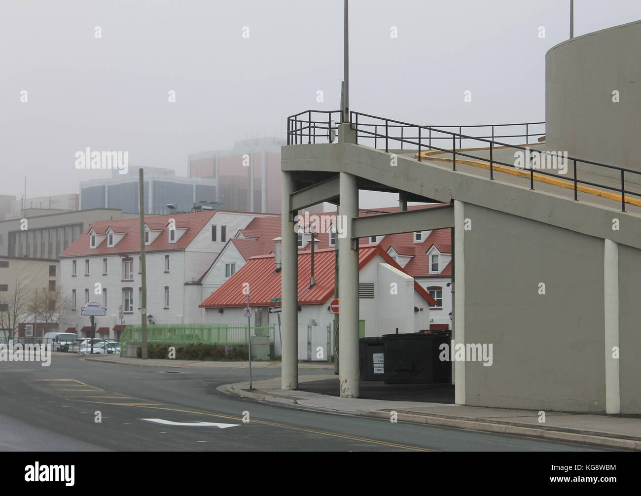Heritage buildings in the fog on Harbour Drive, st. John's, Newfoundland, Modern glass buildings visible through - Stock Image