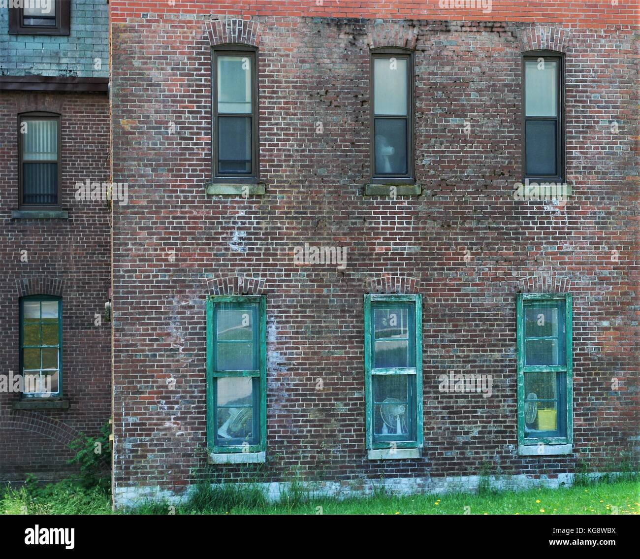Exterior wall of old brick building, with old, wood framed windows - Stock Image